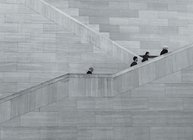 men climbing up stairs black and white