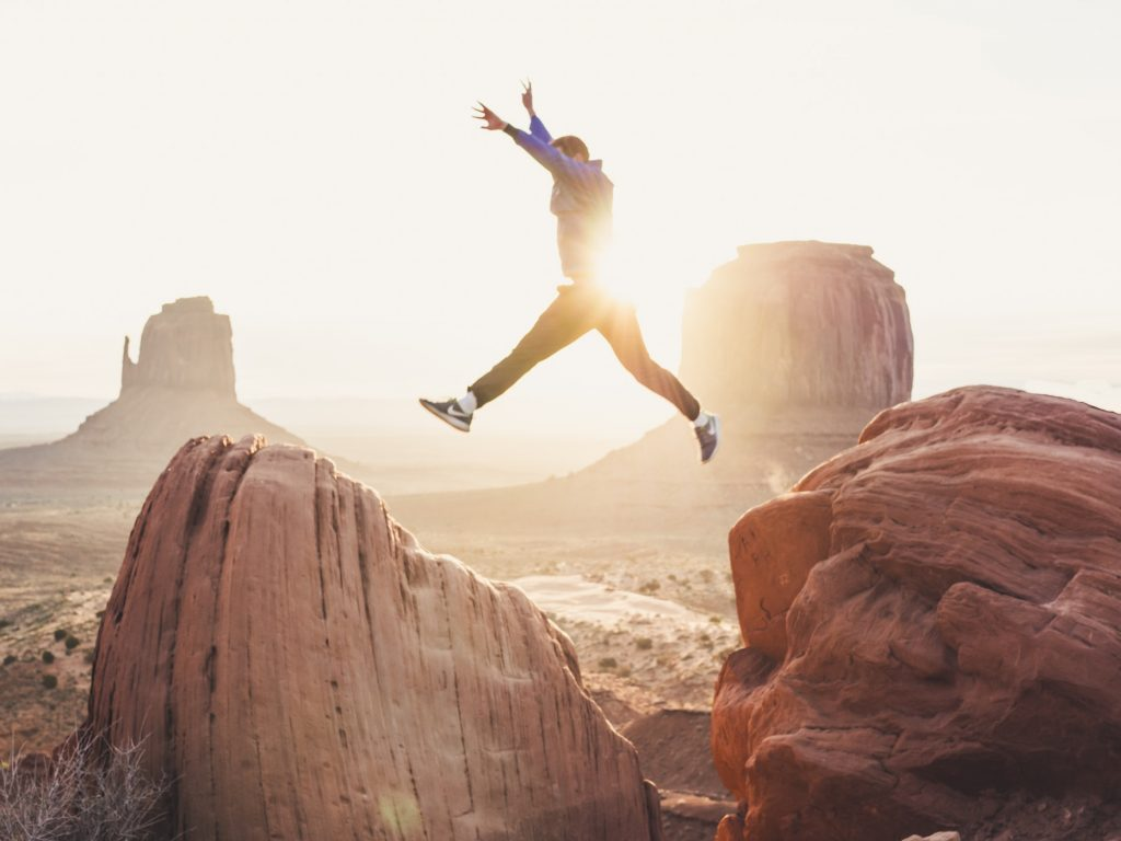 Man jumping from one rock to another on a mountain