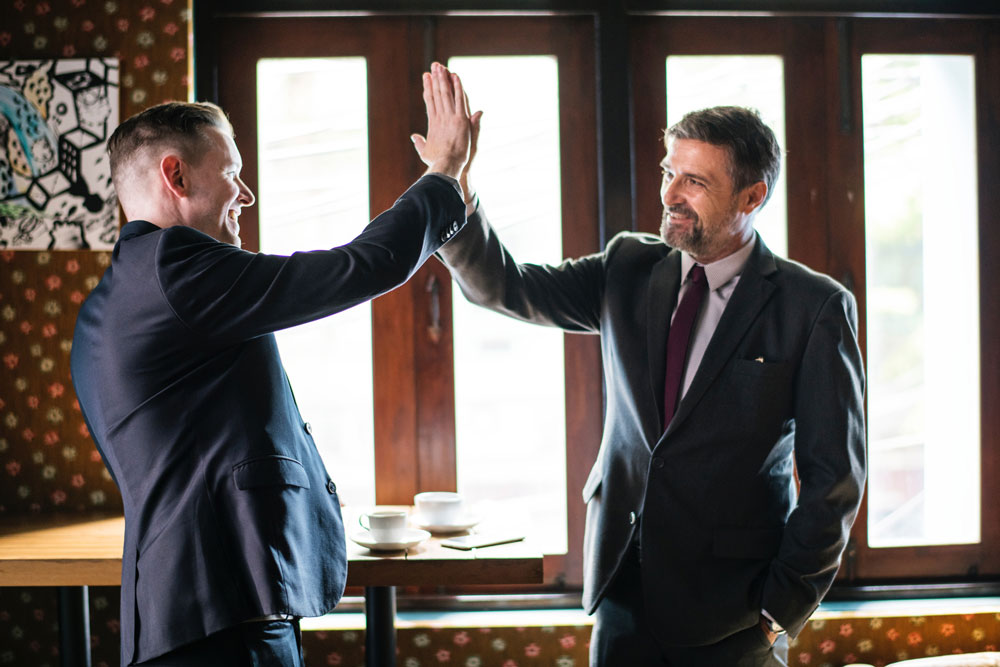 Two men shaking hands over a positive customer experience
