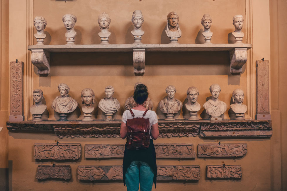woman looking at shelves with old sculptures