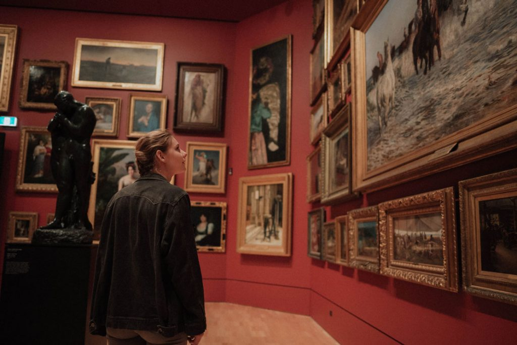 woman admiring paintings at museum