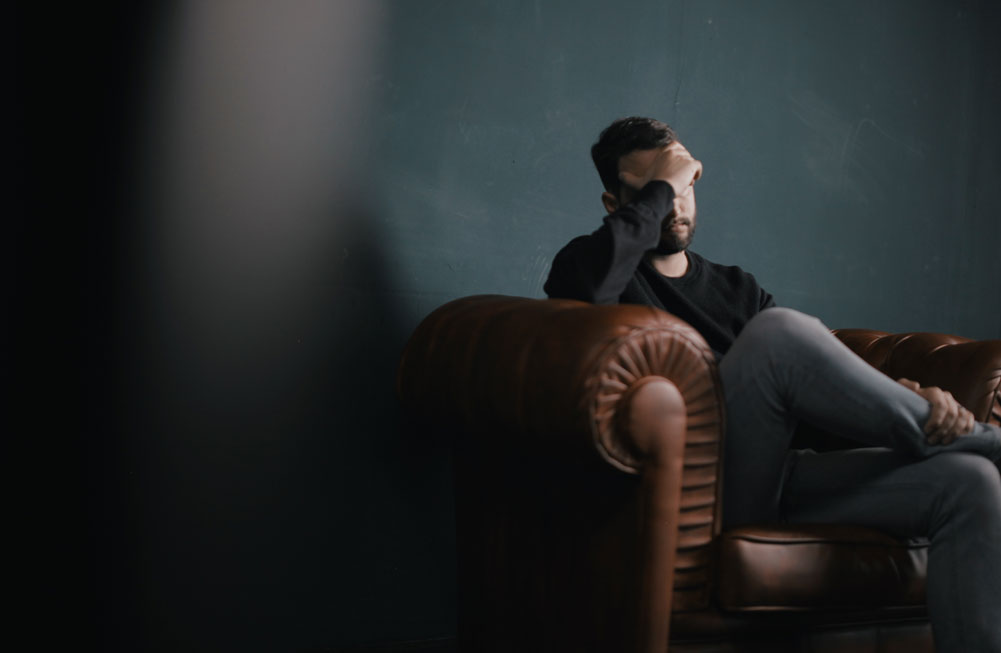 Stressed man sitting on leather sofa