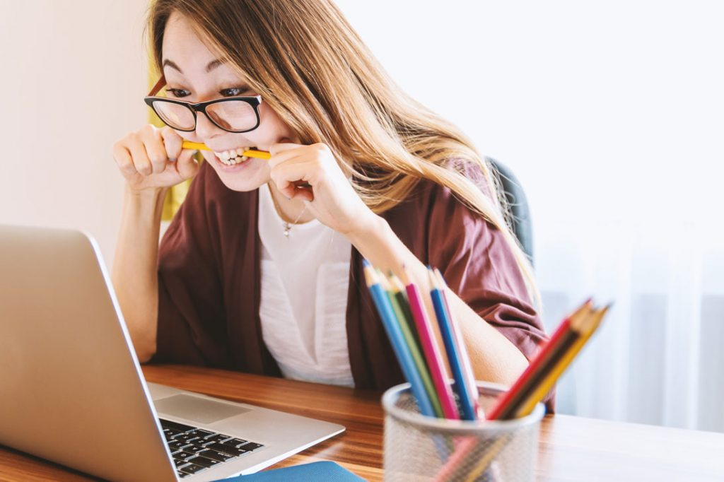 woman biting pencil sitting at desk in front of computer