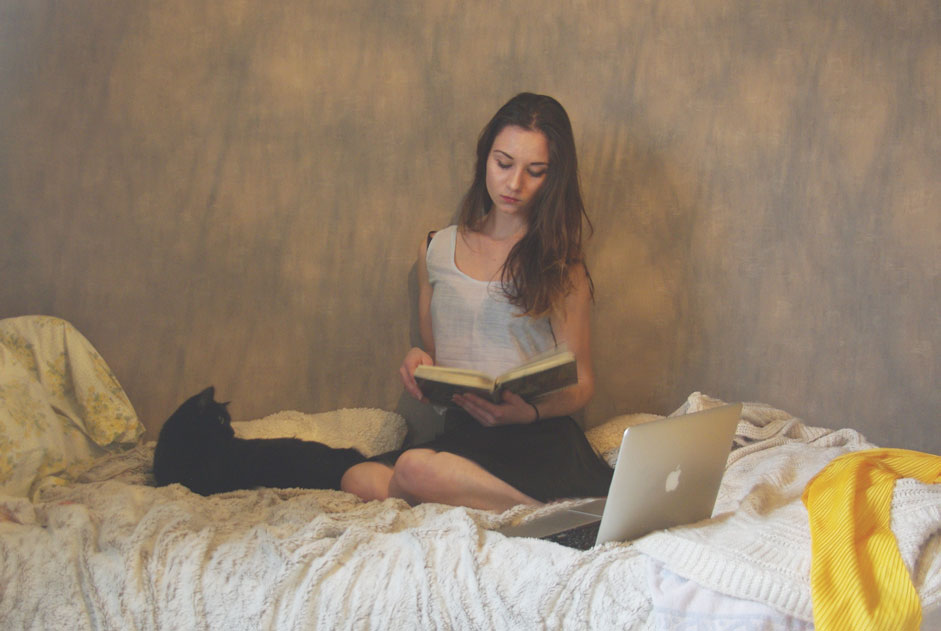 girl reading a book on her bed