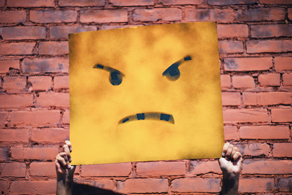 Angry face on yellow board