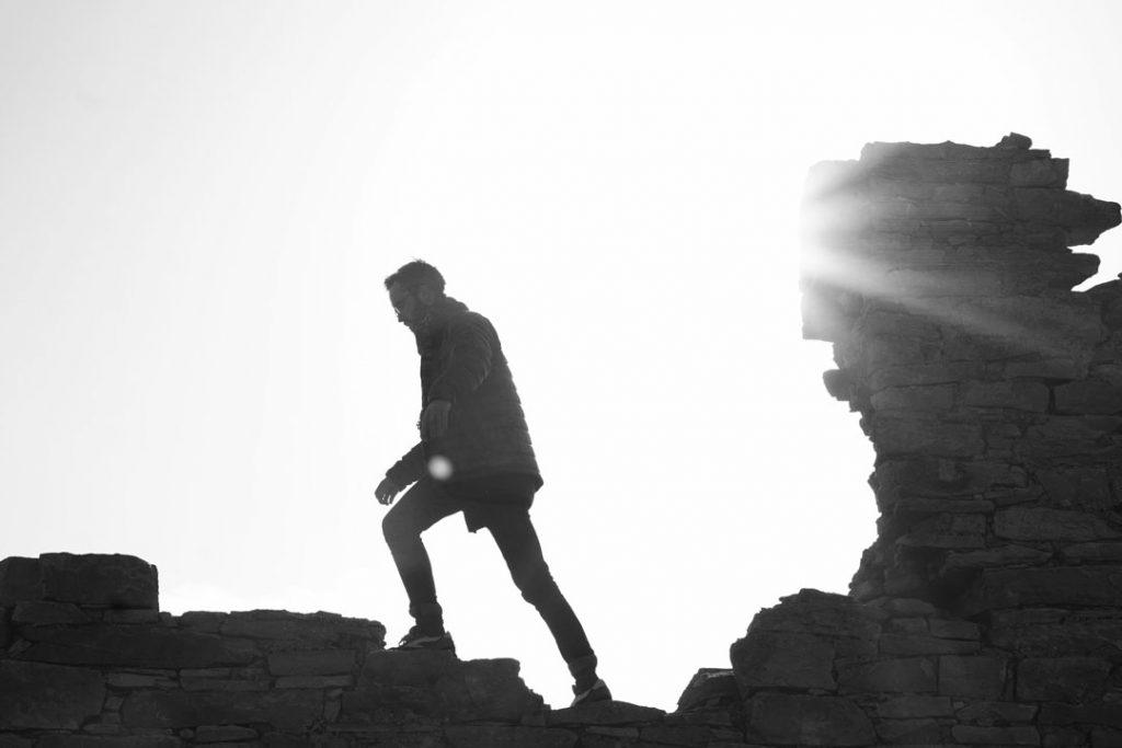 man walking along ancient walls