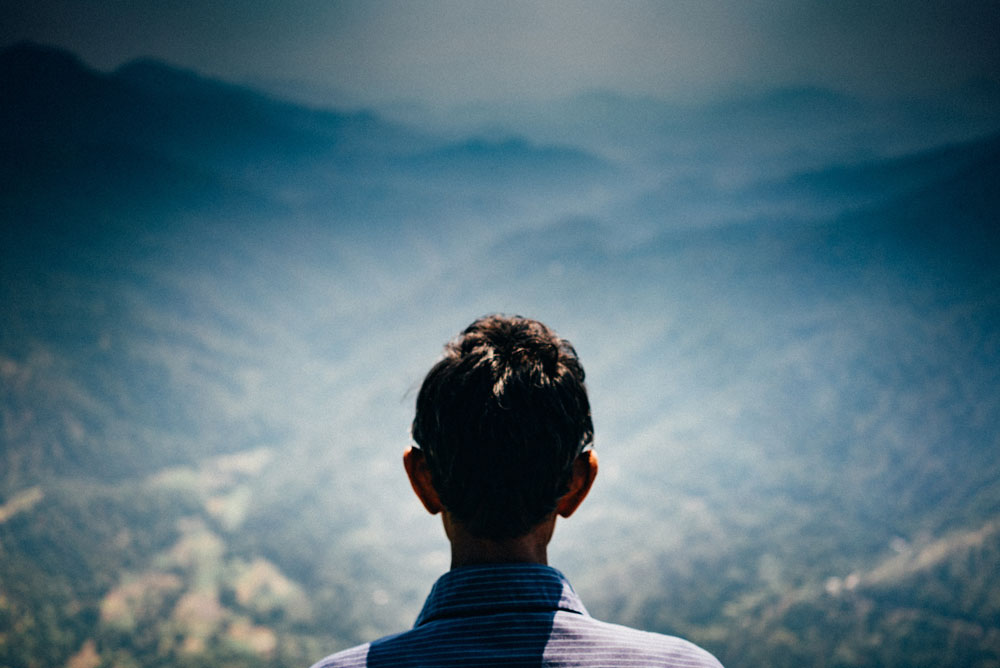 Man looking out over a valley and mountains