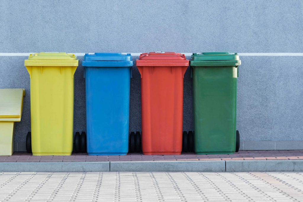 four recycling bins: yellow, blue, red and green