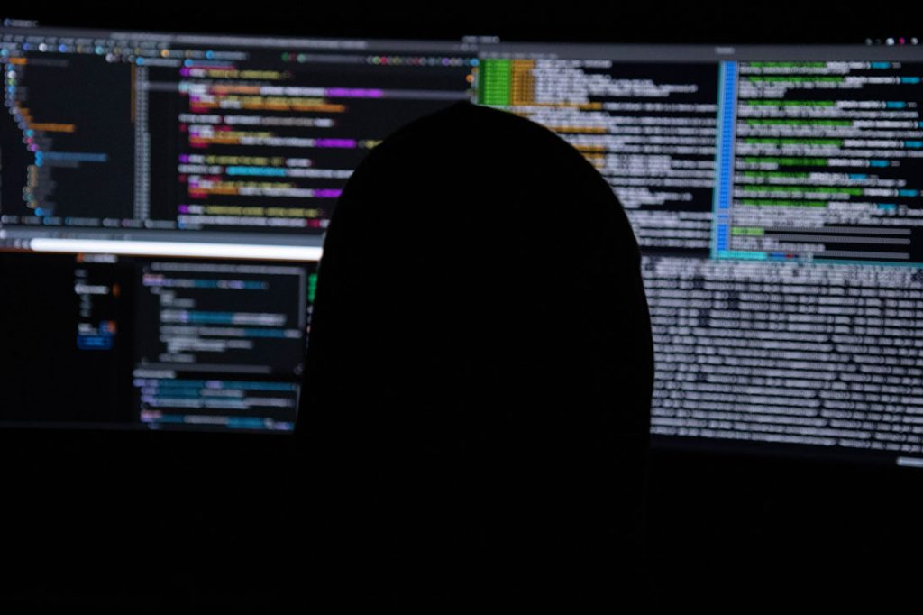 hooded person in front of computer screens with code