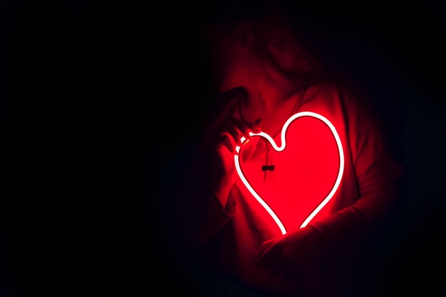 A person holding a heart shaped light