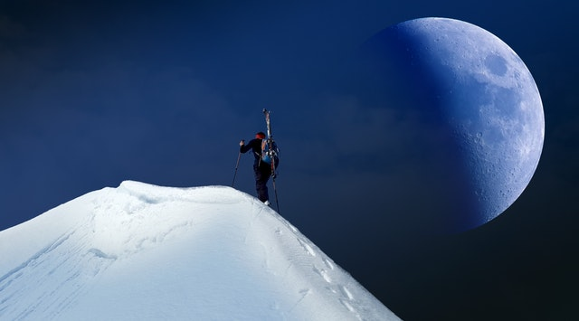 man climbing a mountain full of snow with the moon in the sky
