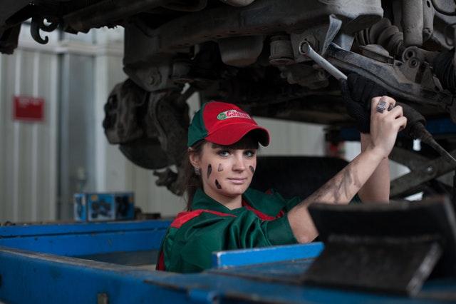 woman mechanic under a car
