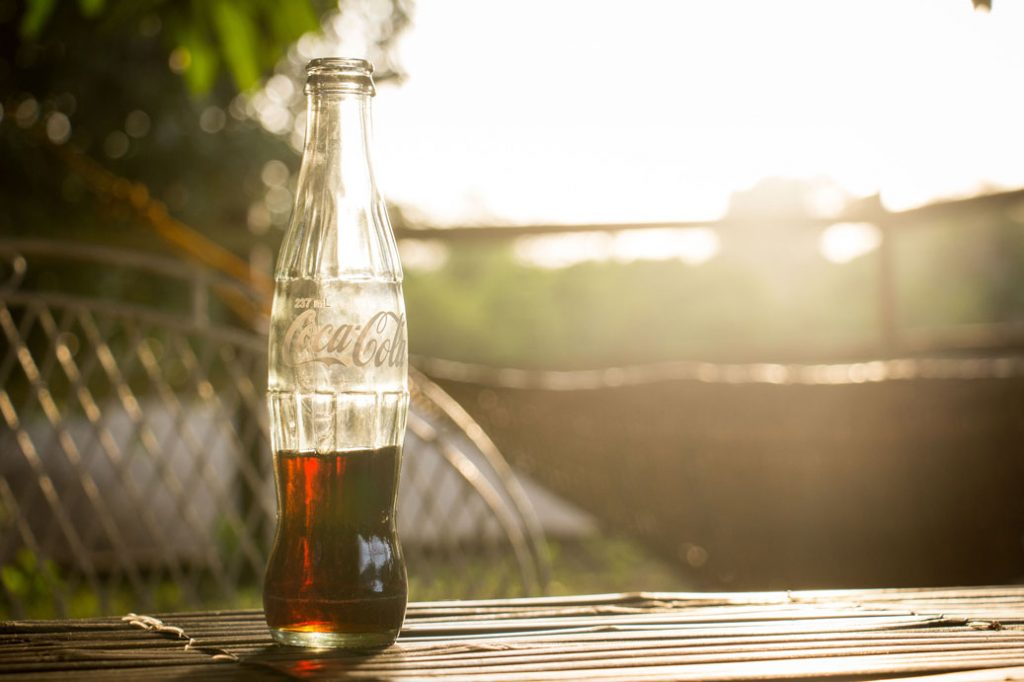 coca-cola glass bottle on a table outside