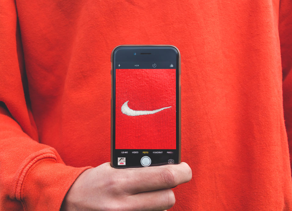 man holding phone with nike logo