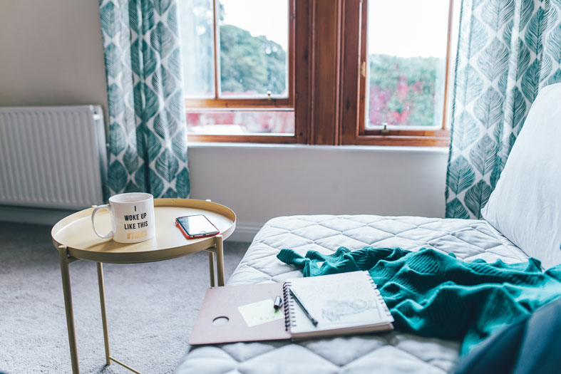 room with a window a sofa and a notebook