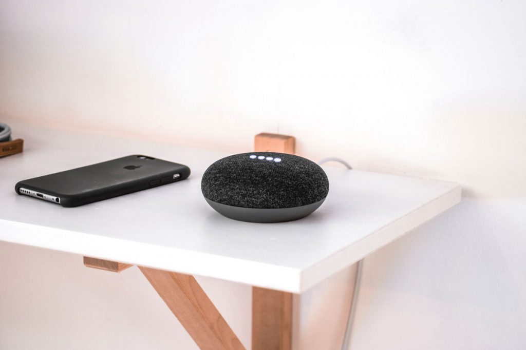 iphone on a table next to a Google home speaker