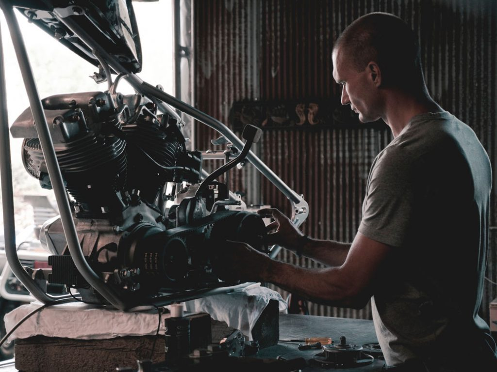 man repairing car engine