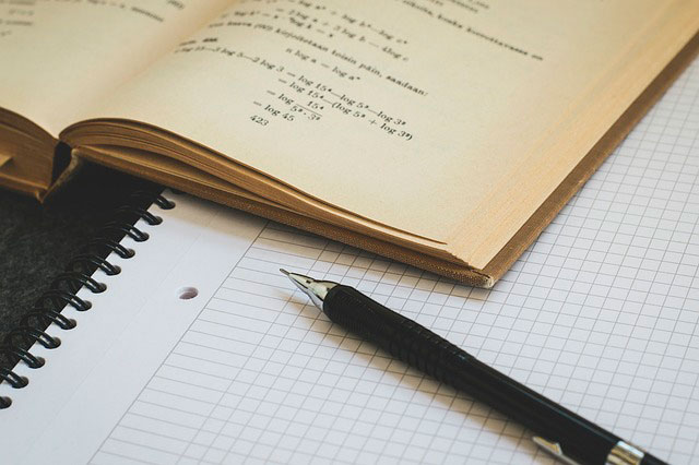 open maths textbook with pen and notebook