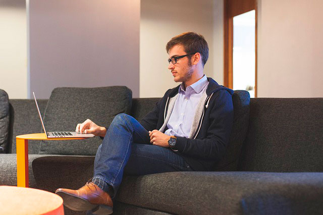 man sitting on a sofa looking at laptop
