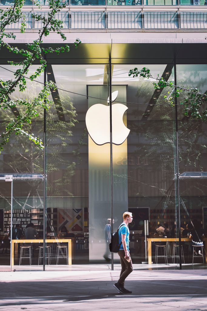 Man walking past Apple store