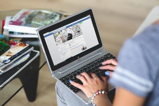 Woman on laptop on Facebook