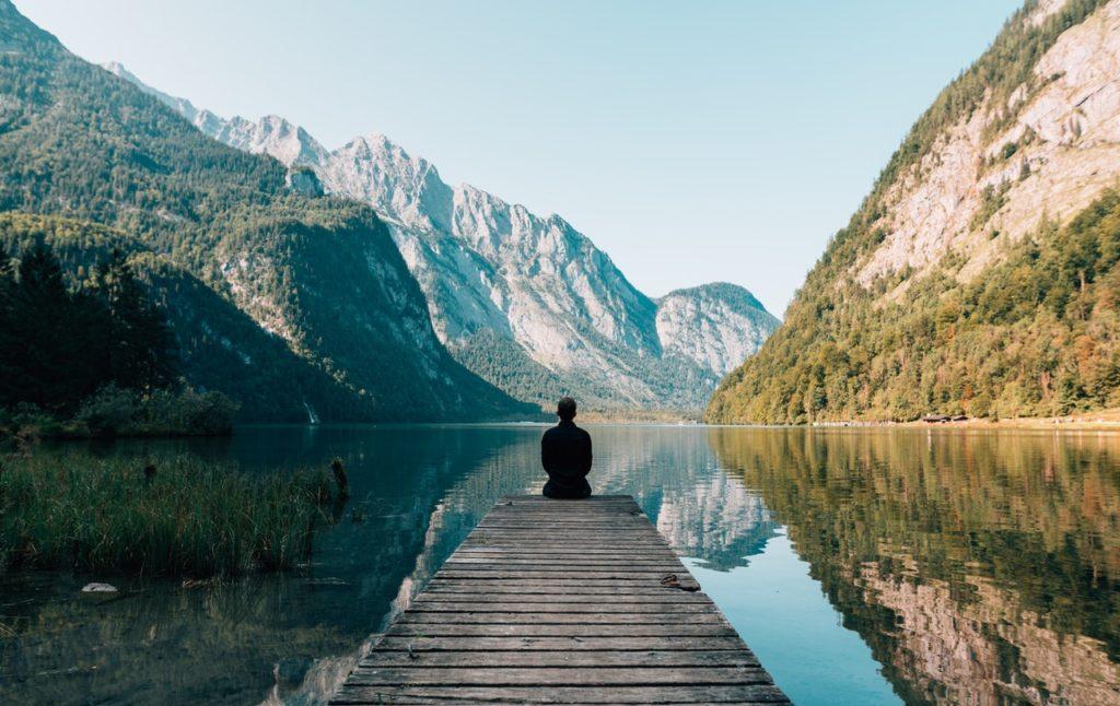person sitting at a lake