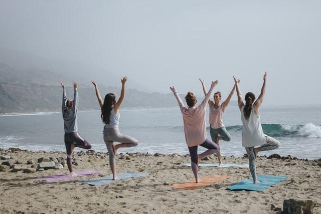 Women practising yoga on the beach