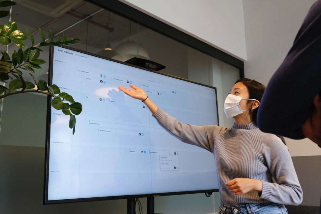 Person with mask pointing at screen