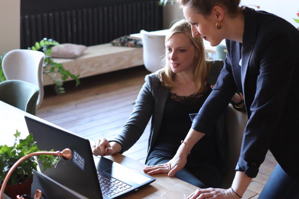 two women sitting around a computer