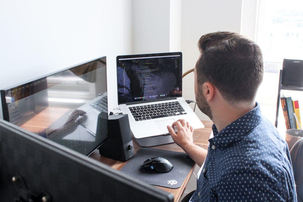 men working on multiple computers