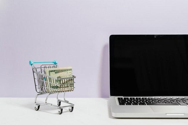 mini shopping cart full of money next to laptop