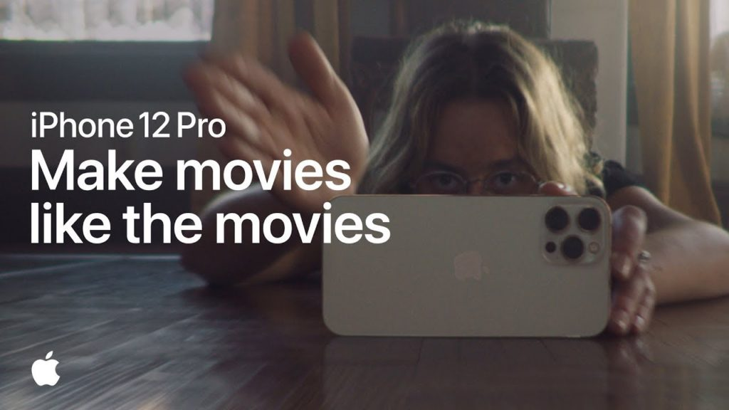 """Ad for iPhone 12 Pro. The ad has a picture of a young woman lying on the floor with her phone, filming something. The ad says """"iPhone 12 Pro """"Make movies like the movies."""""""