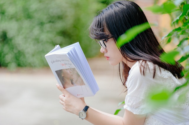 Side profile of girl reading book