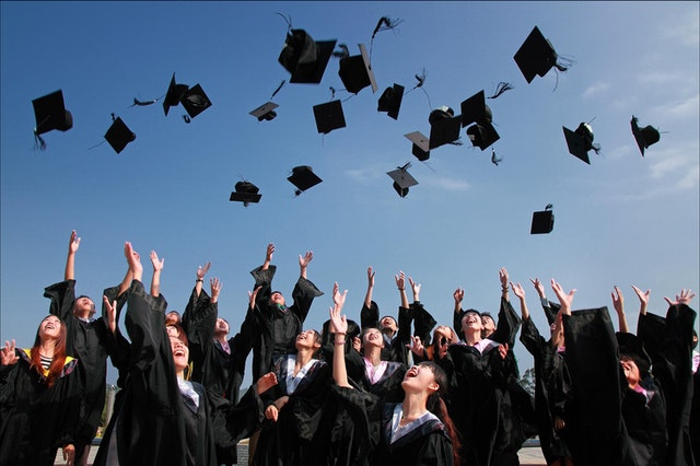 Group of students in graduation ropes throwing their caps into the air