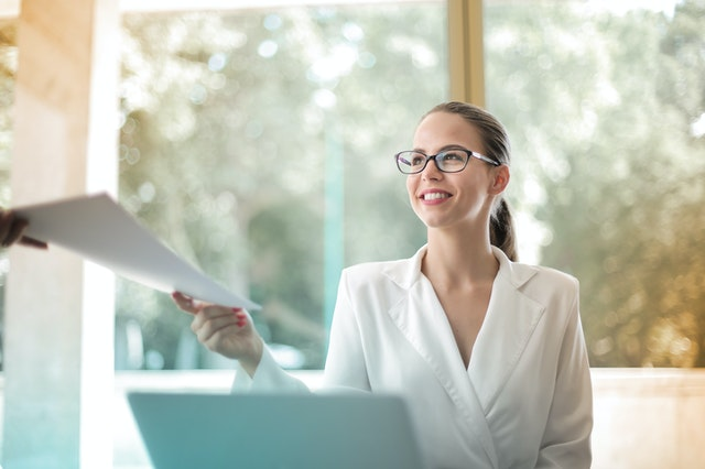 Smiling woman receiving stack of papers