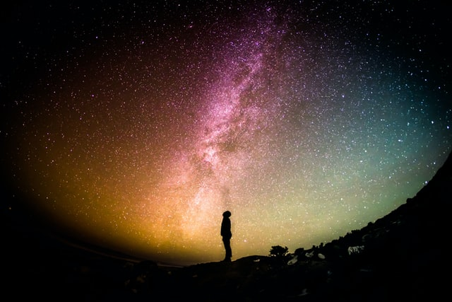 Silhouette of person looking up at starry sky