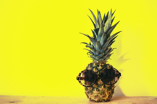 Pineapple wearing sunglasses against yellow background