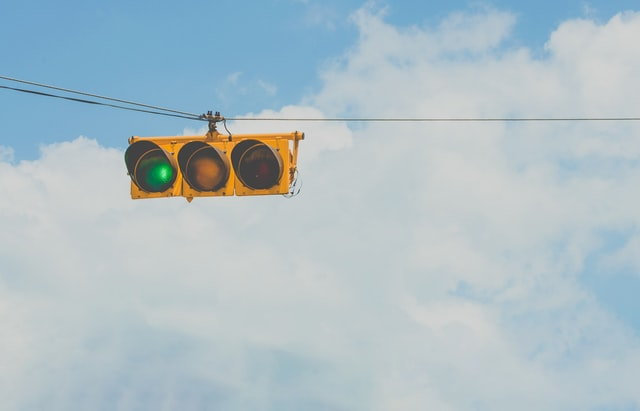 green traffic light against backdrop of clouds
