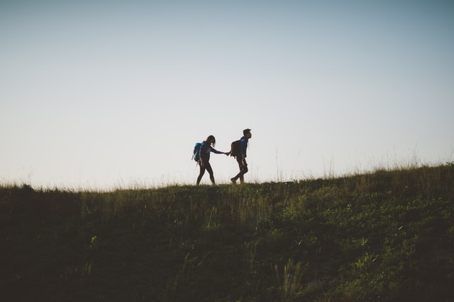 silhouettes of two people walking in the wilderness, one leading the other