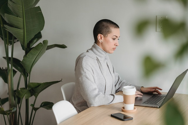 young person on laptop with coffee at side