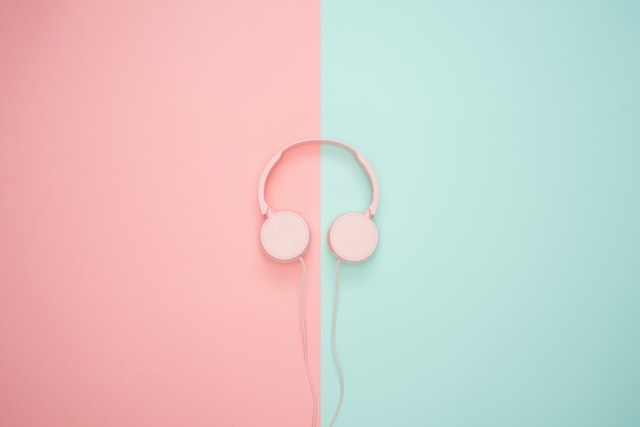 pink over-the-ear headphones on blue and pink background