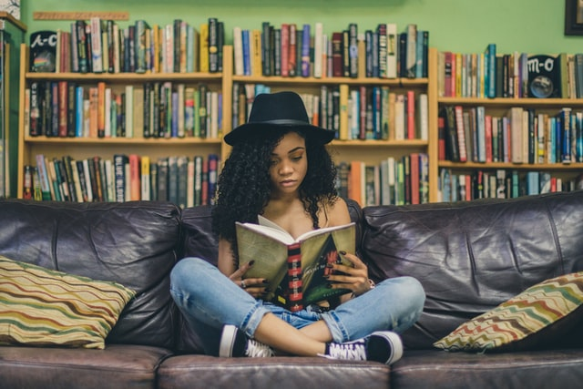woman sitting on couch reading