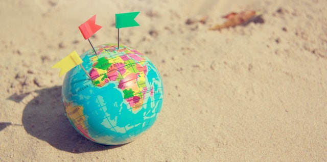 globe with flags marking locations on it on a sandy surface