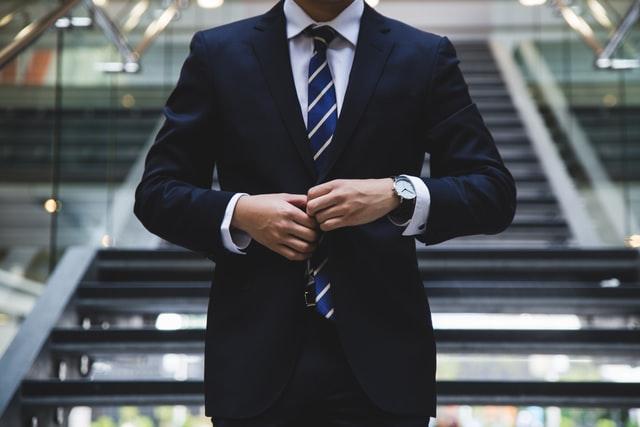 torso of white man in suit adjusting tie