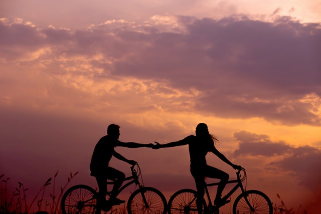 silhouettes of people riding bikes and holding hands