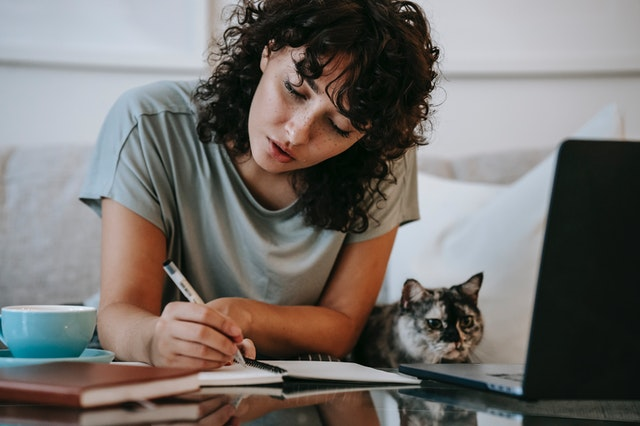 woman working from home with notebook and laptop. there is a cat next to her