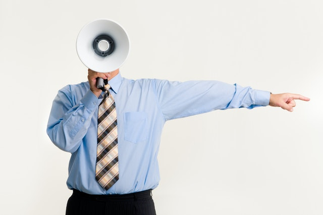 man in business attire with megaphone in front of his face, pointing to the side