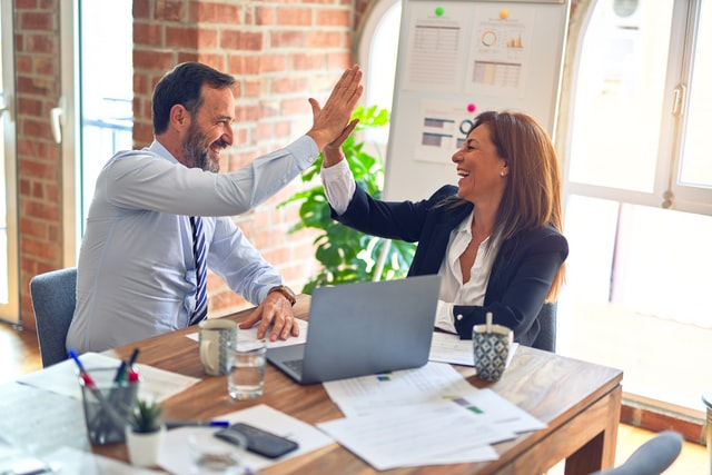 man and woman in business attire sit at a table and high five