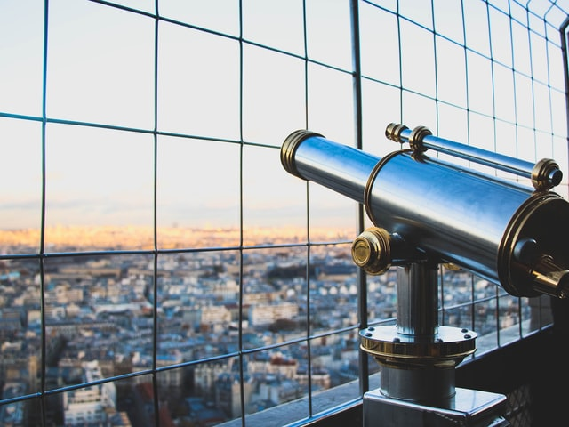 a telescope pointed out over a city through metal wire fence