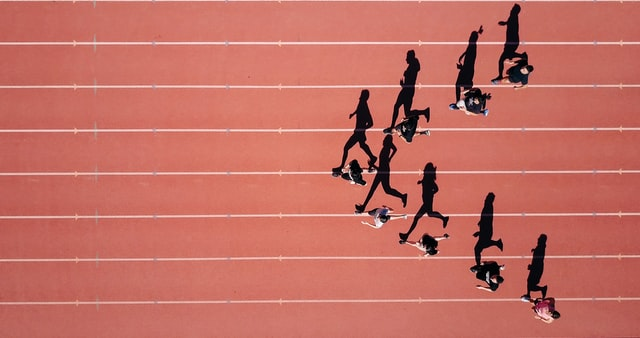 A birds eye view of a team walking in a v-formation on a running track